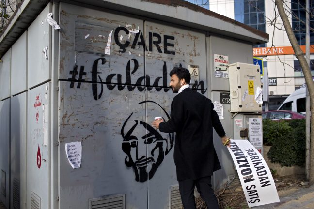 Sertaç Taşdelen, a Turkish entrepreneur and creator of the fortune telling app Faladdin, removes a poster that was hiding graffiti created by his team advertising his app in Istanbul, Turkey
