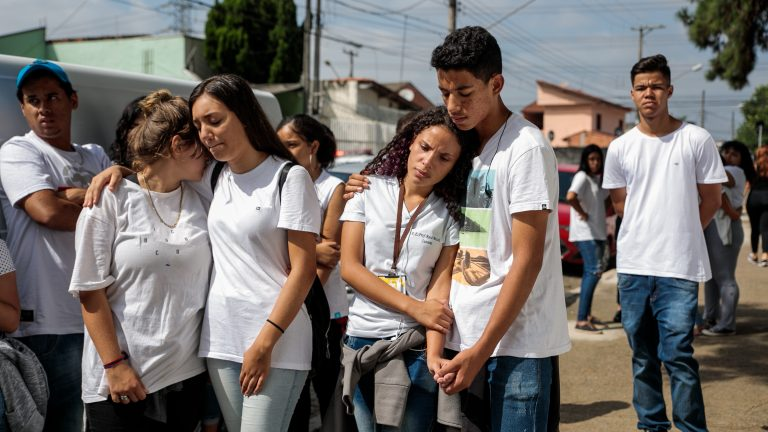 Students gather up in front of the Raul Brasil State School with a group of musicians to sing and pray in honor of those who were killed in the mass shooting a year ago. March 13, 2020. Suzano, SP.