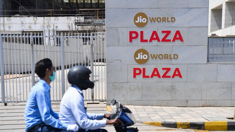 Motorists ride past the Jio World Centre during a government-imposed nationwide lockdown as a preventive measure against the spread of the COVID-19 coronavirus, in Navi Mumbai on April 22, 2020. - Facebook has taken a $5.7 billion stake in the Jio digital platforms business of India's richest man Mukesh Ambani, the two sides said on April 22, marking one of the biggest foreign investments in the country. The deal will give the US social media giant a 10 percent stake in Jio Platforms, part of Ambani's Reliance Industries empire.