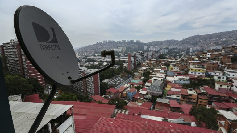 A DirectTV satellite hangs over a roof in Venezuela.