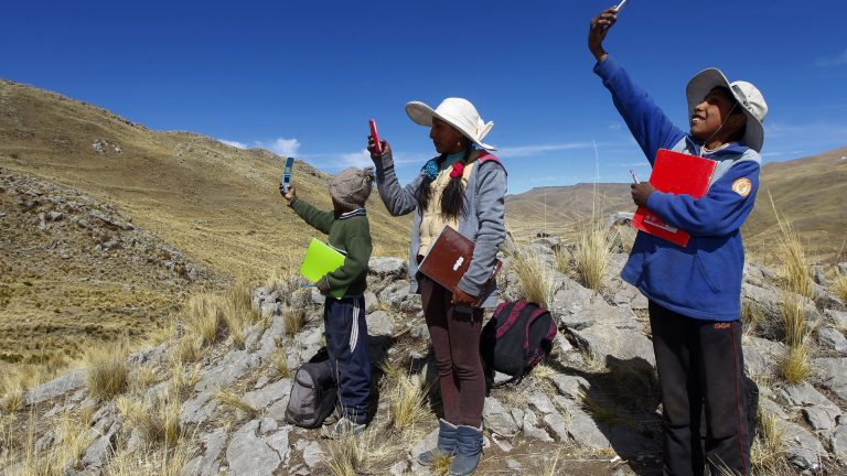 Children search for signal on top of a hill while trying to attend a virtual class during the coronavirus pandemic in the remote highlands of the Peruvian Andes.