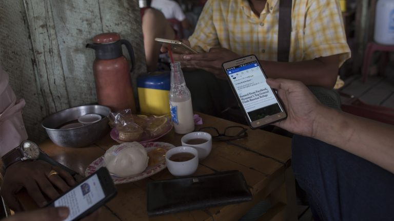 Myanmar people gather for refreshement at a teashop in Yangon on August 31, 2018 many hangout to chat and browse facebook with their mobile phone. - Baffled, hurt or indignant, many inside Myanmar are struggling to digest a week of opprobrium heaped on their country by the UN and even Facebook over the treatment of the Rohingya, a stateless Muslim group whose plight elicits little sympathy in the Buddhist-majority nation.