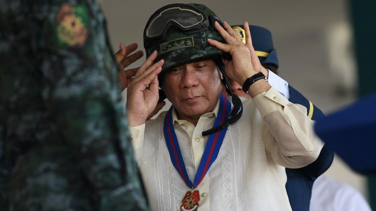 Philippine Philippine President Rodrigo Duterte wears a helmet given to him by the Special Action Force (SAF) unit of the Philippine National Police (PNP) during the 116th anniversary of the PNP at its headquarters in Manila on August 9, 2017.