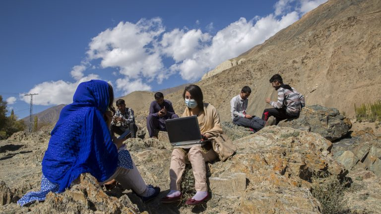 Students use their cellphones near a tower after hiking up to get better internet signals as they face a lot of issues with internet connectivity in their area in Yasin, Gilgit, Pakistan on October 5, 2020. Saiyna Bashir for Rest of World