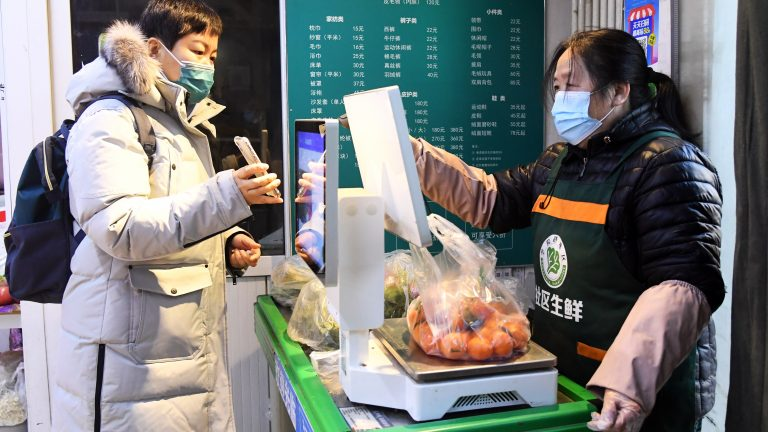 BEIJING, Jan. 16, 2021 -- A resident pays for goods at a neighborhood supermarket in the Xueyuanlu sub-district of Haidian District, Beijing, capital of China, Jan. 16, 2021. With the Chinese Lunar New Year approaching, Beijing's Xueyuanlu sub-district has adopted multiple methods to ensure vegetable supplies to its residents. (Photo by Ren Chao/Xinhua via Getty)