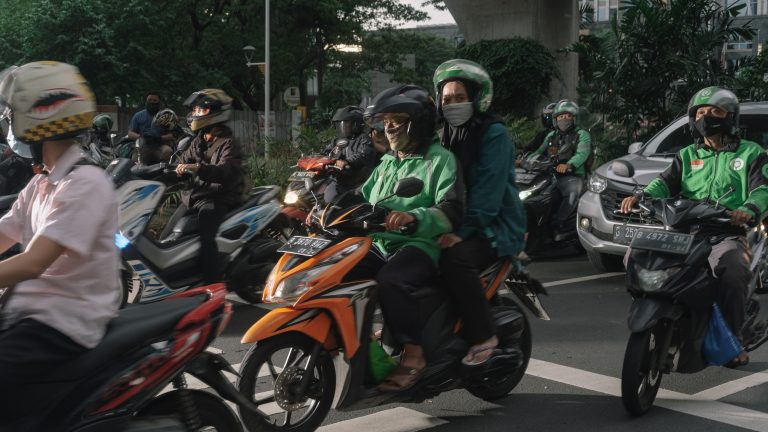 A Gojek rider with his passenger pass the street during rush hour in Kuningan, south Jakarta.