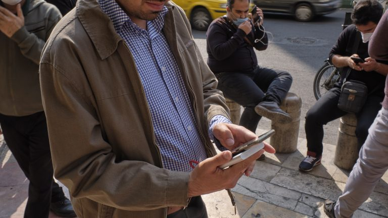 An Iranian street money changer uses a smartphone to check the price update for the U.S. Dollar as he stands on a street-side in Tehrans business district on October 10, 2020. U.S. Dollar has risen again. You may see the price under 300,000 IRR for each Dollar on the electronic board displayed at the currency exchange shops, but the real USD price was 300,000 IRR for buy and 3,250,000 IRR for sale on each Dollar, A street money changer told the photographer. (Photo by Morteza Nikoubazl/NurPhoto via Getty Images)