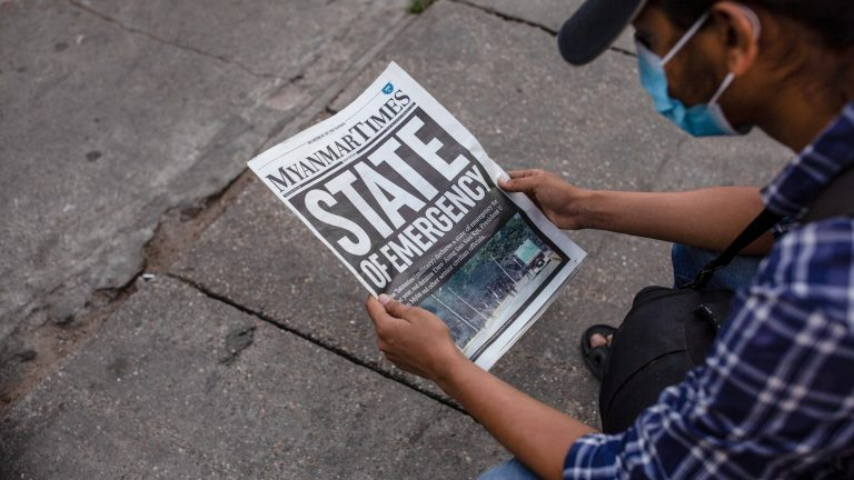 YANGON, MYANMAR - 2021/02/02: A man wearing a face mask seen reading a the Myanmar Times newspaper with the headline 'State of Emergency' a day after the Myanmar's military detained the country's de facto leader Aung San Suu Kyi and the country's president in a coup. (Photo by Aung Kyaw Htet/SOPA Images/LightRocket via Getty Images)