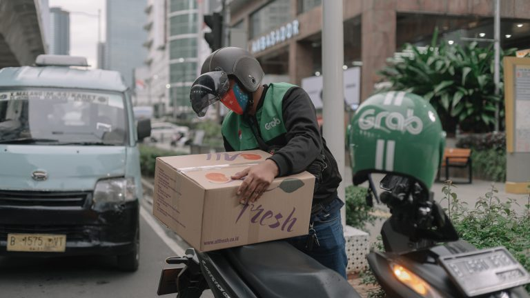 A Grab driver in Kuningan, South Jakarta, arranges a box to be delivered to a customer.
