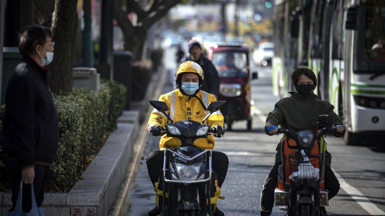 A food delivery courier for Meituan waits at a traffic signal light in Shanghai.