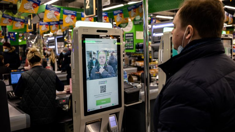 An X5 group representative demonstrates a facial recognition payment system at a  self-checkout machine in a Perekrestok supermarket in Moscow on March 9, 2021. - Russia's X5 group, the country's leading food retailer, announced on March 10 the launch of a facial recognition payment system, the latest expansion of a technology that has sparked privacy and security concerns. (Photo by Dimitar DILKOFF / AFP) (Photo by DIMITAR DILKOFF/AFP via Getty Images)