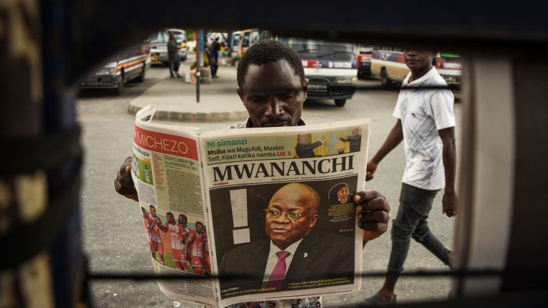 TOPSHOT - A man reads a newspaper with a headline announcing the death of Tanzania's President John Magufuli in Dar es Salaam, on March 18, 2021. - Tanzania was plunged into mourning on March 18, 2021 over the death of President John Magufuli following weeks of uncertainty over his health, with his swing to authoritarianism leaving a divided legacy. (Photo by - / AFP) (Photo by -/AFP via Getty Images)