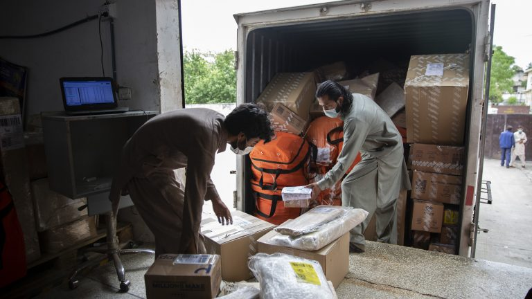 Employees offload and scan items from a truck containing shipment Daraz warehouse, Pakistan's largest online shopping and e-commerce marketplace in Islamabad, Pakistan on April 16, 2021.