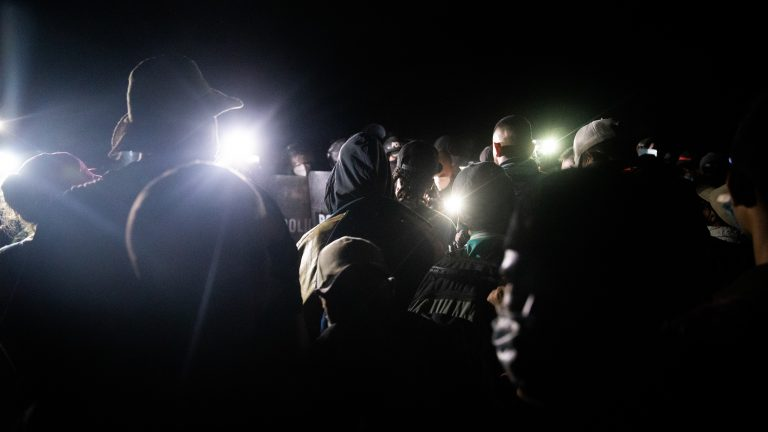 Police and migrants argue back and forth as the caravan continues to push into the wall of riot shields in pitch black darkness.