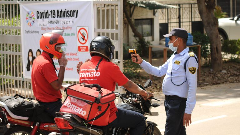 GURUGRAM, INDIA - MARCH 25: A security guard is seen thermal screening two zomato delivery personel outside the DLF phase-2 entry date on the first day of the nationwide lockdown due to coronavirus, at Akashneem marg, near Sikanderpur metro station on March 25, 2020 in Gurugram, India. Prime Minister Narendra Modi on Tuesday announced a complete lockdown of the entire country for 21 days in an unprecedented drastic measure to try halt the spread of coronavirus as the number of cases in the country crossed 500. (Photo by Parveen Kumar/Hindustan Times via Getty Images)