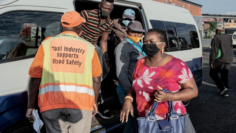 South Africa Taxi Drivers' Union member (L) checks that all the passengers of a mini bus taxi wear the protective mask at the Bara taxi rank in Soweto, Johannesburg, on December 17, 2020. (Photo by LUCA SOLA / AFP) (Photo by LUCA SOLA/AFP via Getty Images)