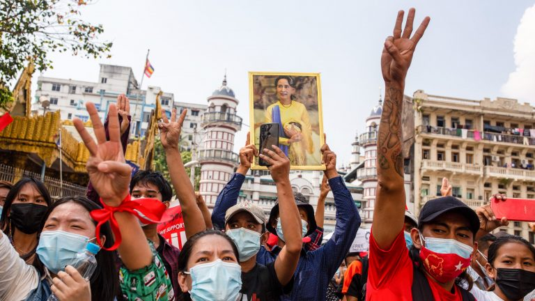 YANGON, MYANMAR - 2021/02/07: Protesters make the three finger salute while holding a portrait of Aung San Suu Kyi in front of the Sula Pagoda during a demonstration against the military coup.