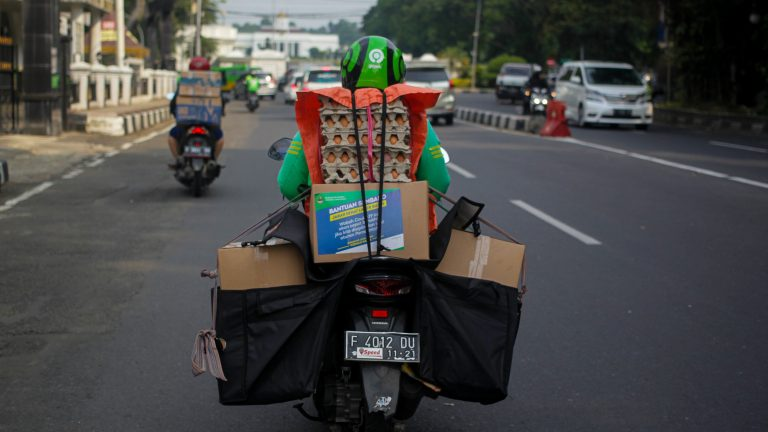 Gojek driver distributes foodstuffs to residents affected by COVID-19 outbreaks, in Bogor, Indonesia, June 5, 2020. The Indonesian government distributes food aid to people affected by Coronavirus outbreaks, through online transportation operators. (Photo by: Aditya Saputra/INA Photo Agency/Universal Images Group via Getty Images)