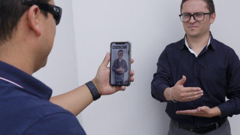 Карлос Обандо и Хьюго Якоме демонстрируют функцию распознавания языка жестов в приложении SpeakLiz, которая превращает классический язык жестов в современную форму общения, преобразовывая его в голос и текст в реальном времени с помощью камеры телефона.