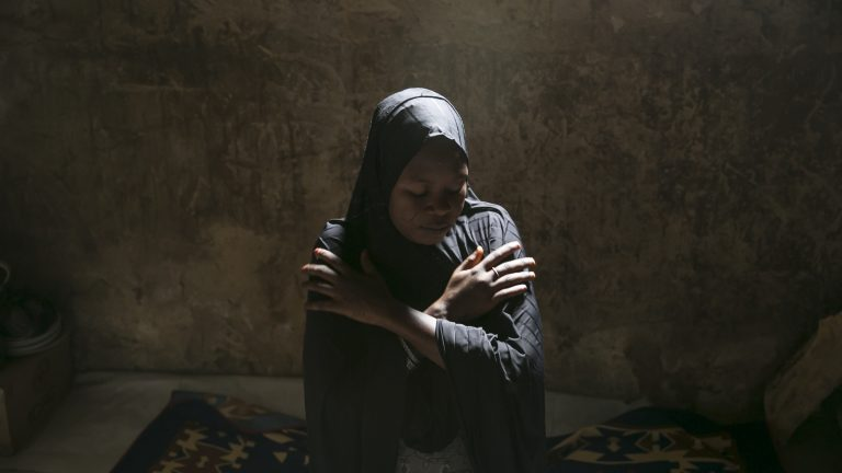 Aisha BG, 28, brushes off her shoulders as she prays in her rented mud house in the outskirts of Maiduguri, Nigeria, April 29, 2019. When Boko Haram attacked her village in Bama Local Government in 2014, they killed her husband and kidnapped two children. She walked to the Sambisa Forest to save her children, but ended up getting married to a commander for survival. Two and half years later, she was joined by her children as the commander died and she refused to marry another fighter by claiming she had contracted HIV. She is pregnant again with a member of civilian joint task force; however, she refused to marry him and he has disappeared. She expects to give birth in June.
