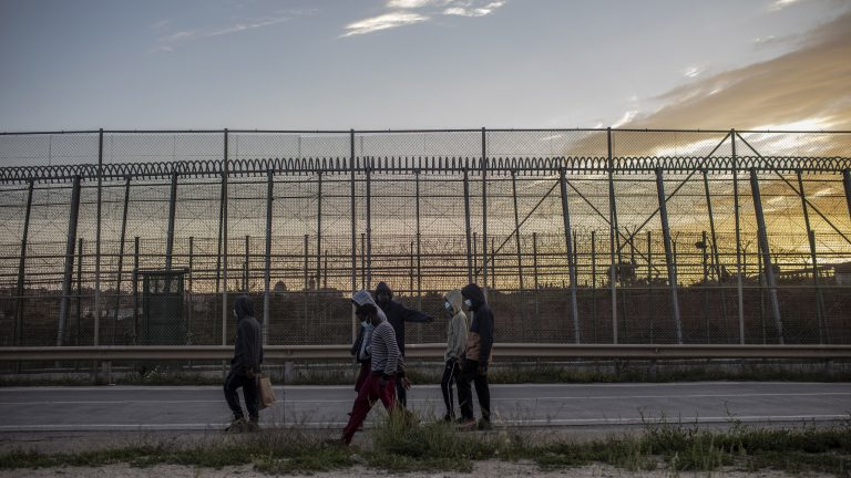 """MELILLA, SPAIN - APRIL 29: A group of unaccompanied minors walk their way back """"La Purisima"""", an old fortress reconverted into a minor migrant temporary stay center, near the fence in the Autonomous city of Melilla, Spain. April 29. 2021"""