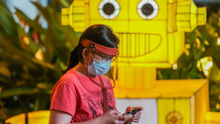 MANILA, Dec. 22, 2020 -- A woman wearing a face mask and a face shield uses her mobile phone in front of a Christmas display at a mall in Manila, the Philippines, Dec. 22, 2020. (Photo by Rouelle Umali/Xinhua via Getty) (Xinhua/Rouelle Umali via Getty Images)