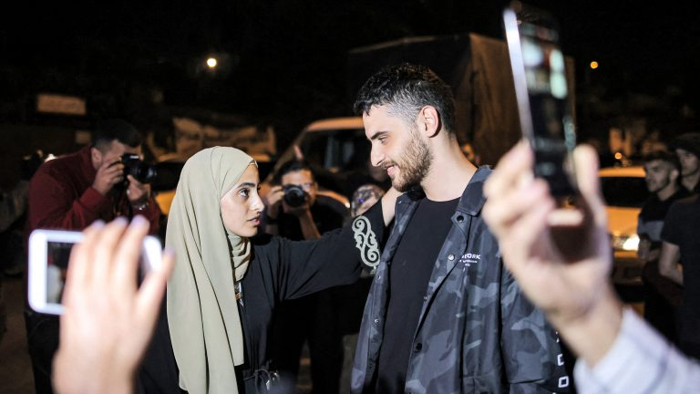 Palestinian activist twins, Mona and Mohammad el-Kurd, look at each other.
