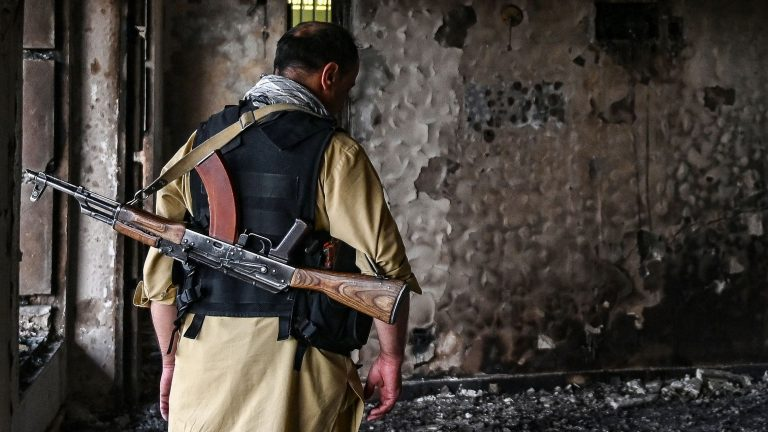 An Afghan security personnel inspects inside a building a day after a car bomb explosion in Kabul.